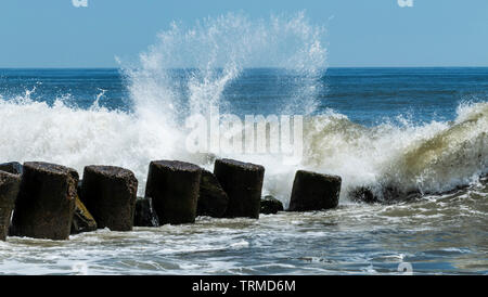 Waves breaking and splashing onto a pier off of the coast of Long Island New York. - Stock Photo