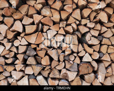Neatly stacked stock firewood is dried and is ready for the winter to use in the fireplace. - Stock Photo