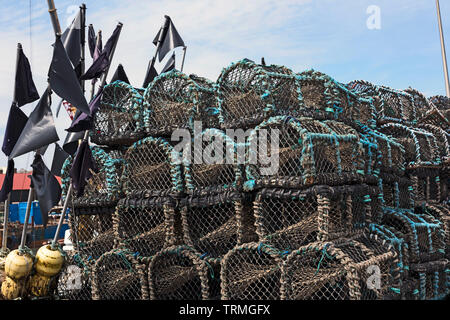 Lobster pots, (creels) and marker buoys piled up on the quayside of Arbroath Harbour, Angus, Scotland, UK - Stock Photo