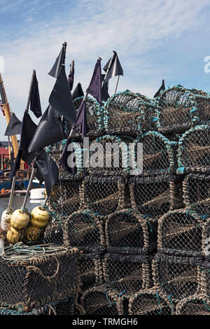 Lobster pots, (creels) and marker buoys piled up on the quayside of Arbroath Harbour. - Stock Photo