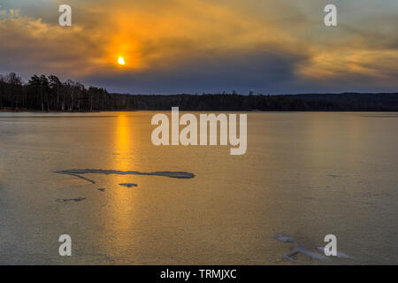 Beautiful sunrise with dramatic overcast cloudy orange sky over frozen ice covered Lake Uspen in Sweden - Stock Photo