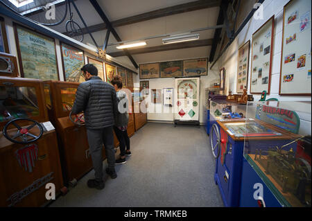People playing old 'Penny in the slot' arcade games at the Lakeland Motor Museum, Newby Bridge, Cumbria, UK. - Stock Photo