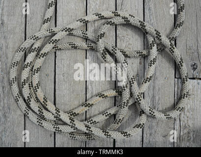 Marine rope coiled on a wooden dock and tied to a metal dock