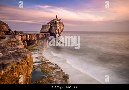 Man standing on top of Pulpit Rock at sunset, Portland Bill on the Isle of Portland near Weymouth on Dorset's Jurassic Coast. England. UK. - Stock Photo