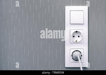 Light switch , power sockets, lead and plug on gray wall. Close-up. - Stock Photo