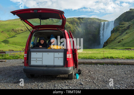 Couple relaxing in a red minivan in sleeping bags with opened back door. Skogafoss waterfall in the background, Iceland - Stock Photo