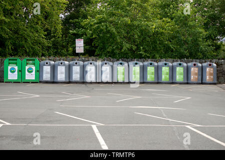 Row of recycling containers bins in empty car park Ireland - Stock Photo
