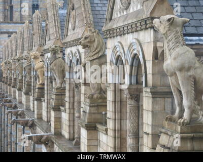 Photo of the ornate terracotta stonework and statues high up on a façade of the Natural History Museum, an iconic London landmark in Romanesque style - Stock Photo