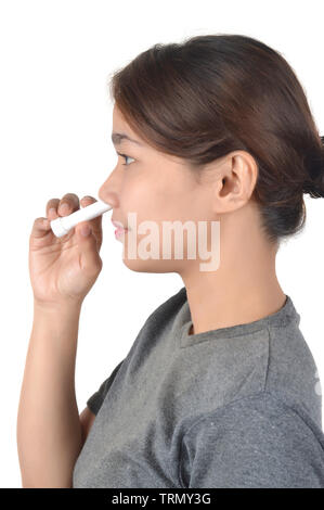 Asian girl holds nose inhaler isolated on white background - Stock Photo