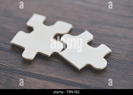jigsaw puzzle on wooden background top view / Two jigsaw piece connecting business solutions success and strategy concept