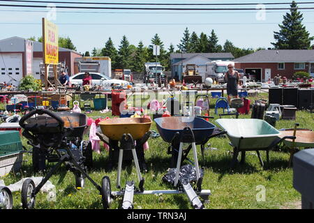 Rusty wheelbarrows and other assorted junk at Stittsville's Carp Road Flea Market, Carp, Ontario, Canada. - Stock Photo