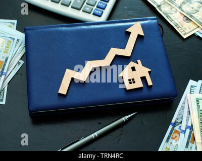 Property investment concept. Model of house and arrow. - Stock Photo