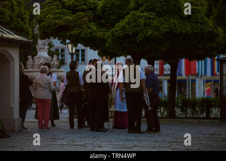 Altoetting,Bavaria-June 8,2019: A priest talks with musicians from a brass band before masson a Saturday evening - Stock Photo