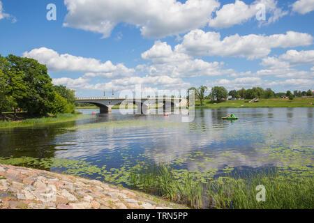 City Jelgava, Latvian Republic. River Lielupe,  people are driving catamaran. Bridge and water. Jun 9. 2019. Travel photo. - Stock Photo
