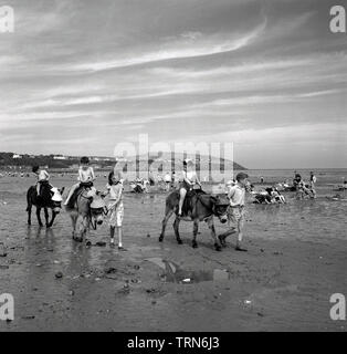 1950s, historical, young children having a donkey ride on a beach, a traditional British holiday activity in this era. - Stock Photo