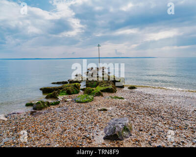 Seaweed covered rocks at low tide on Lee on Solent beach. - Stock Photo