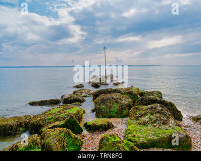 A line of seaweed covered rocks lead out in the the estuary on Lee on Solent beach. - Stock Photo