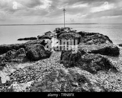 Over wet, seaweed covered rocks and out in the the Solent estuary. Image processed to simulate the tones, contrast and grain of 1970's 35mm film. - Stock Photo