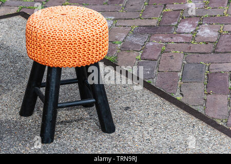 little black stool with orange seat is on the street - Stock Photo
