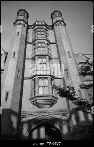 Armstrong Building, Queen Victoria Road, Newcastle upon Tyne, c1955-c1980. A detailed view of the south-east elevation of the Armstrong Building, showing the five storey Tudor style gatehouse with oriel windows and octagonal towers. The building was constructed in 1887-1906, originally as a College of Science for the University of Durham. It is red brick with ashlar dressings, and surrounds an irregular quadrangle. The image focuses on the Tudor style tower of the south-east facade, showing the carriageway arch and four storeys of canted oriel windows above. The corners each have octagonal tow - Stock Photo