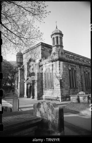 Holy Trinity Church, Wallace Green, Berwick-upon-Tweed, Northumberland, c1955-c1980. An exterior view of the west elevation of the church, seen from the south-west, with the graveyard in the foreground. The church was built in 1648-1652 by a London mason, and its chancel was added in 1855. The image shows the west elevation, which has a central entrance underneath a broken pediment porch, flanked by tuscan columns. Above is a Venetian window, and the  west end of the nave is flanked by two wide buttresses. On the exterior corners of the aisles are octagonal cupolas with domed roofs and cross f - Stock Photo