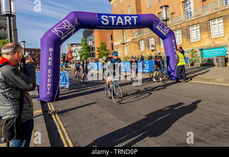 June 2019, Norwich 100 bike ride: Cyclists taking part in the Norwich cycle ride leaving the starting gate to embark on their one hundred mile tour ar - Stock Photo
