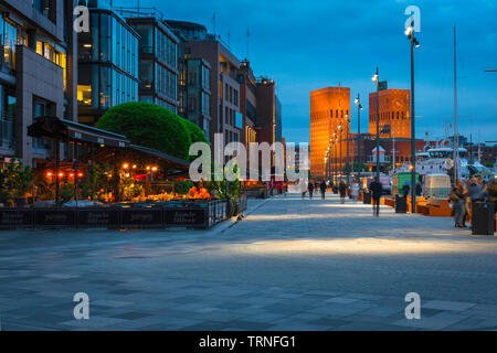 Oslo harbor, view at night of the harbor district (Aker Brygge) in central Oslo with the Town Hall building (Radhus) in the distance, Norway. - Stock Photo