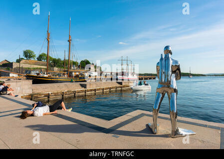 Oslo Norway summer, view of a woman sunbathing beside a sculpture of a silver diver (Dykkar) on a quay in the harbour area (Aker Brygge) of Oslo. - Stock Photo