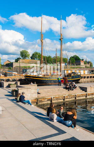 Oslo harbor, view of young people relaxing beside a quay in the harbor area (Aker Brygge) in Oslo on a summer afternoon, Norway. - Stock Photo