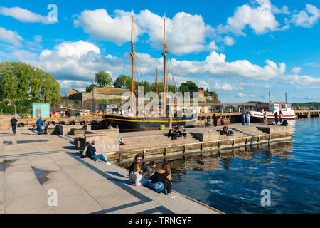 Oslo Norway, view of young people relaxing beside a quay in the harbour area (Aker Brygge) in Oslo on a summer afternoon, Norway. - Stock Photo