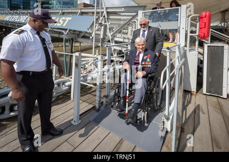 London, UK. 6th June 2019. Imperial War Museum marks 75th anniversary of the D-Day landing on board HMS Belfast. D-Day veterans (Arthur Barnes in chair) from Blind Veterans UK board the HMS Belfast, the ship that led the Allied fleet on D-Day. Credit: Guy Corbishley/Alamy Live News - Stock Photo