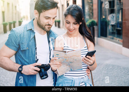 Couple traveling in europe using map and cellular - Stock Photo