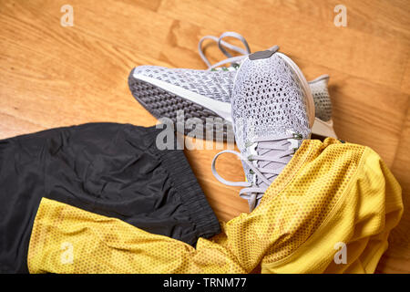 running shoes along with a shirt and shorts on a wooden gym floor - Stock Photo