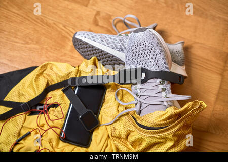 running shoes with a t-shirt, pants and technological accessories on a wooden gym floor - Stock Photo
