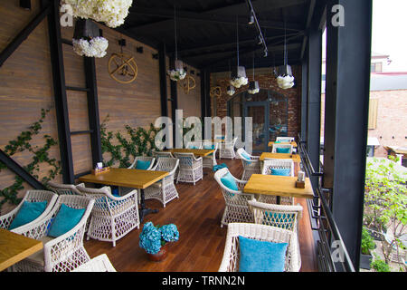 Desert terrace in a city cafe on a summer afternoon, decorated with artificial flowers - Stock Photo