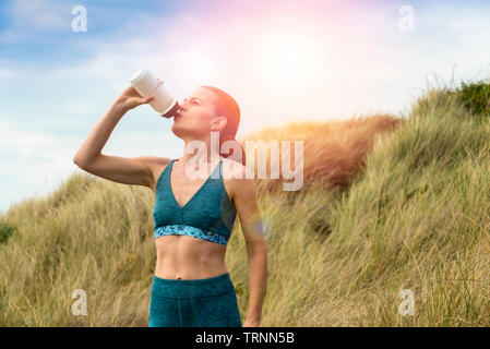 Sportswoman drinking water from a bottle after exercise in the sun - Stock Photo