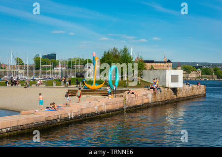 Oslo beach, view of people relaxing on Tjuvholmen City Beach in the harbour area of Oslo, Norway. - Stock Photo