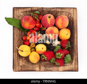 Summer fruits on a wooden plate. Along with fine droplets of water. - Stock Photo