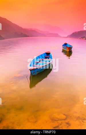 Two Boats parking in Phewa Lake,and Colorful Sunset On Background.Pokhara Nepal - Stock Photo