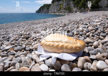 Cornish pasty on shingle beach with sea in background