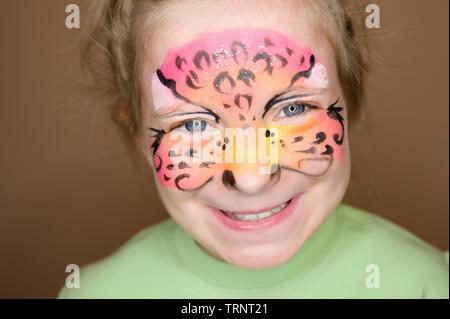 Adorable little girl with colorful painted face. - Stock Photo