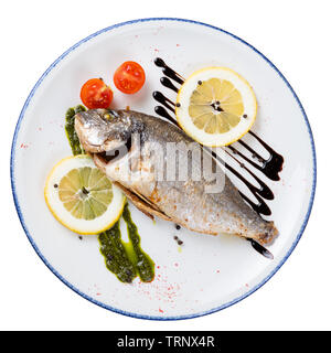 Dorado fried fish on a round plate with a blue border, top view on an isolated background - Stock Photo
