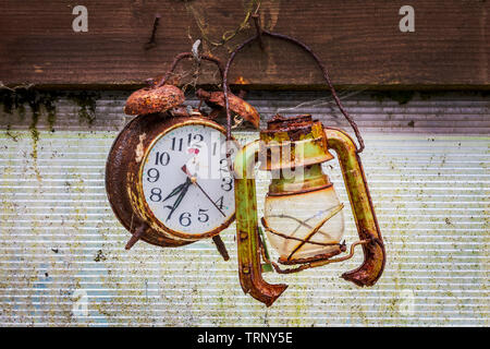 Old and rusty alarm clock hanging on a nail next to an old broken lantern, in a garden shed