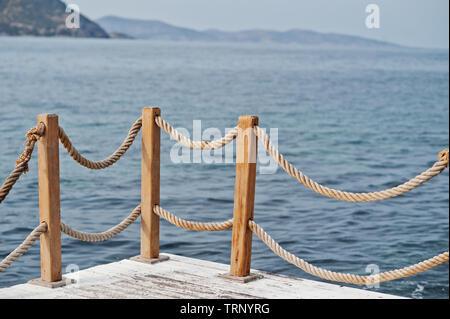 Banister railing on marine rope and wood Turkey Mediterranean sea. - Stock Photo