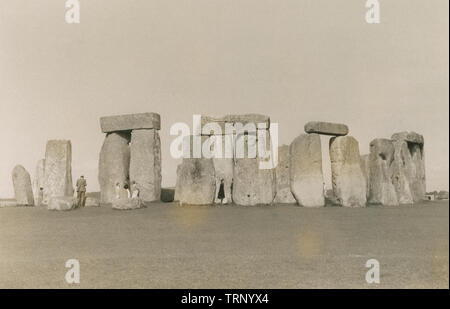 Antique c1950 photograph, tourists at Stonehenge in Wiltshire, England. Stonehenge is a prehistoric monument. It consists of a ring of standing stones set within earthworks in the middle of the most dense complex of Neolithic and Bronze Age monuments in England. SOURCE: ORIGINAL. PHOTOGRAPH - Stock Photo