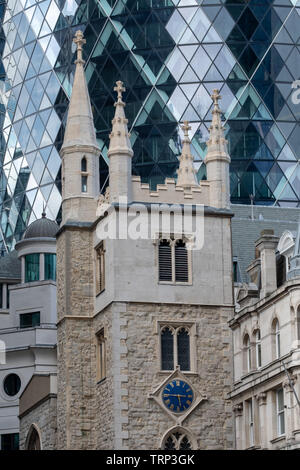 Iconic Gherkin Building, 30 St Mary Axe in the City of London financial district. Historic church of St Andrew Undershaft is in the foreground. - Stock Photo