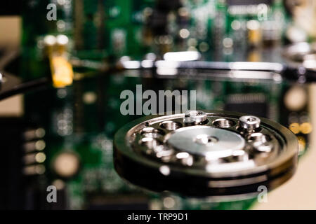 Controller circuit board and hard drive spindle and head actuator in a macro close up of a disassembled hard drive. - Stock Photo