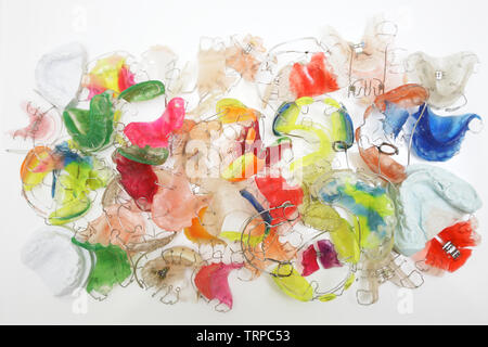 Multicolored frame workpiece dental dentures and plaster casts of teeth on the table in the dental technician's office - Stock Photo