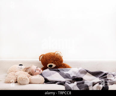Small baby (a boy of three years old) is lying on the sofa under the rug with a teddy bear toys. Selective focus. - Stock Photo
