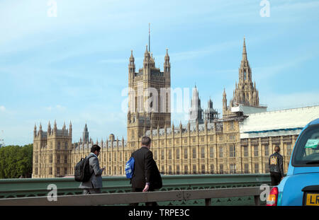 View of Houses of Parliament & pedestrians walking on Westminster Bridge next to barrier City of Westminster, Central London England UK  KATHY DEWITT - Stock Photo